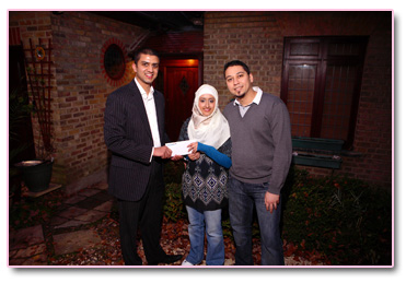 Adeem Younis presents Adam and  Safiyya with their Umrah tickets.